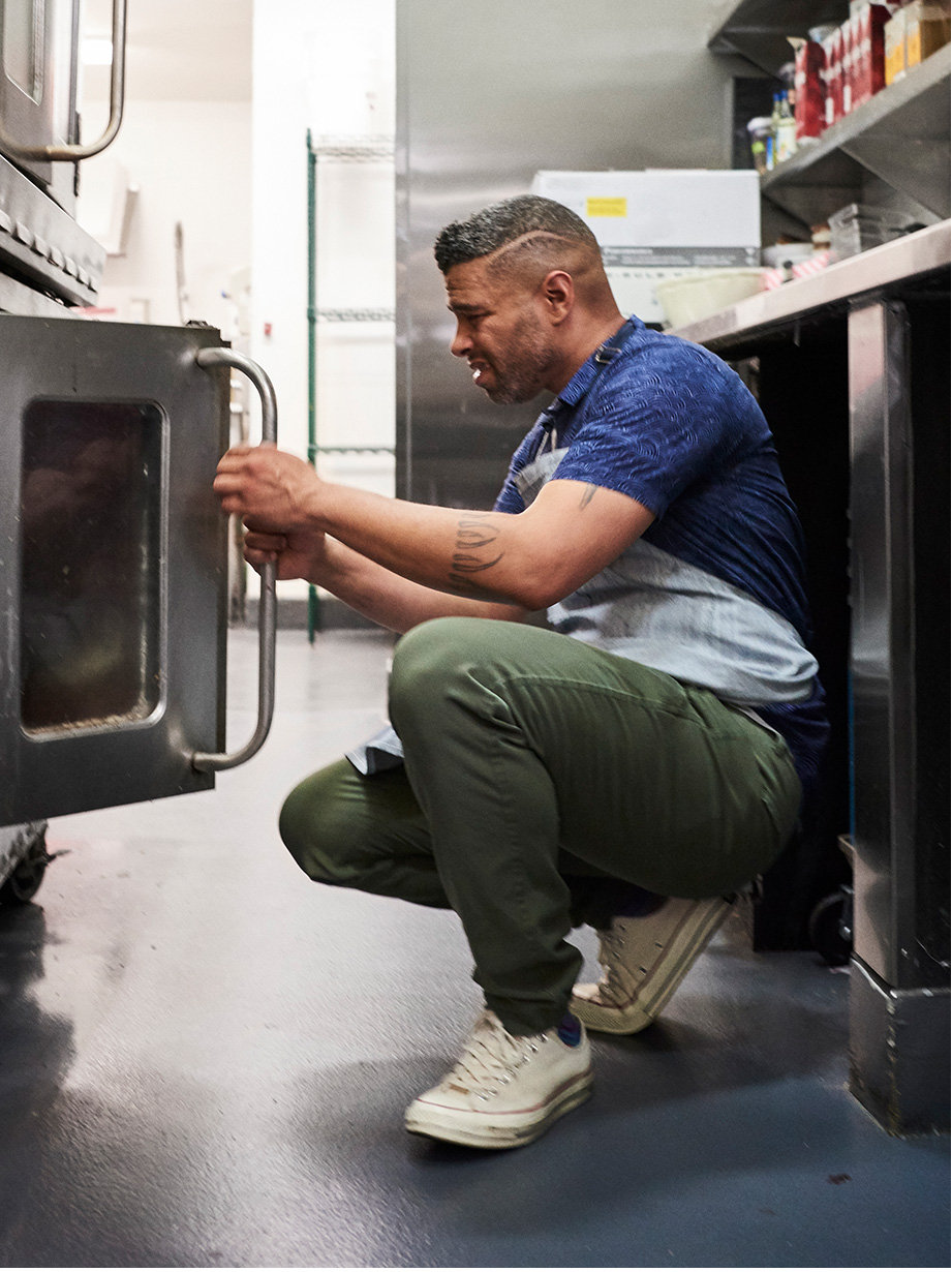 Dante looking at his grill oven wearing Resort Shirt and Dockers Alpha Jogger with Smart 360 Flex