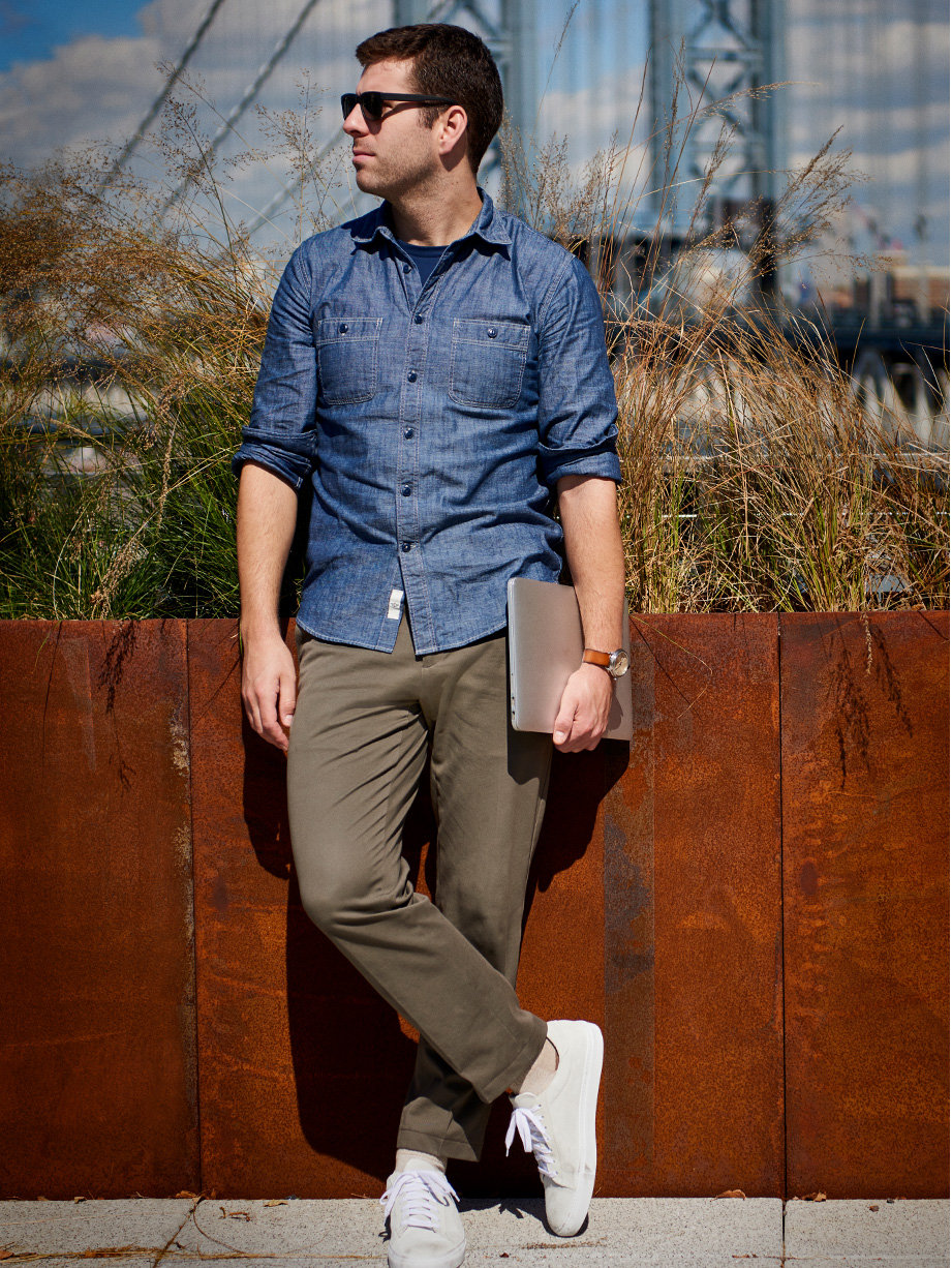 Zach standing beside a wall wearing Downtime khaki, Chambray Shirt and white sneakers