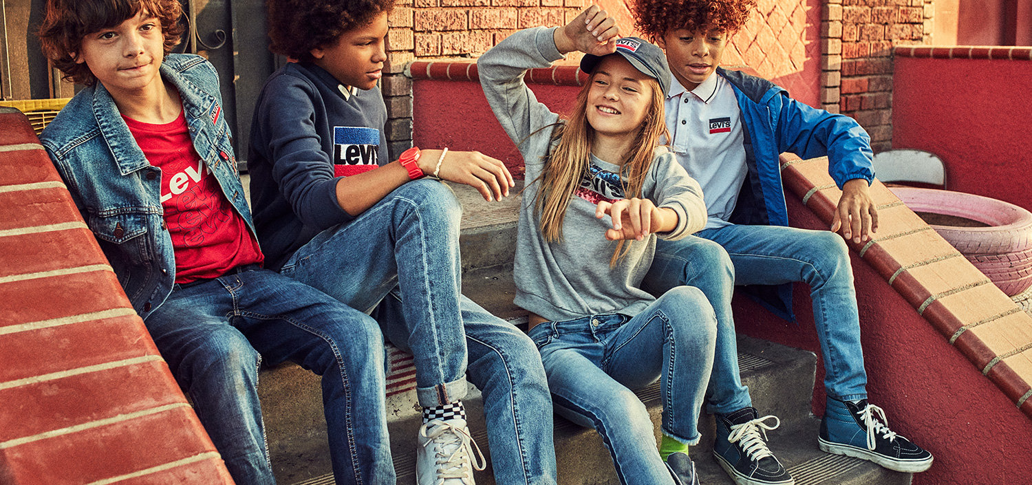 Girl on the left wearing Levis Trucker jacket and grey batwing tee, Buy on the right wearing levis cap, trucker jacket and white levis batwing tee